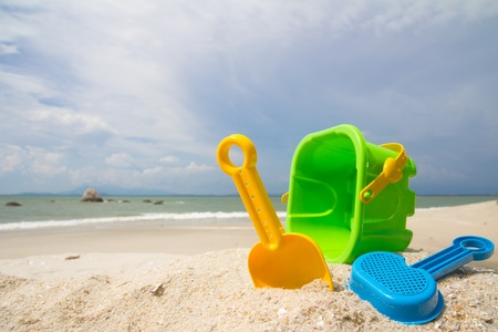 Childs bucket, spade and other toys on tropical beach against blue sky photo