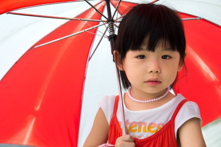 Small little kid hold a red umbrella