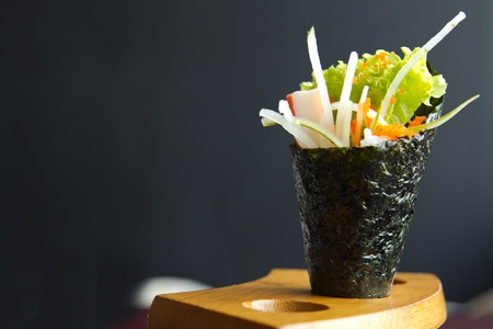 Japanese food, California hand roll hold in a wooden fixture
