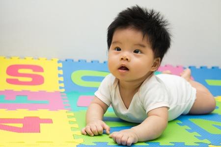 바닥에 크롤 링하는 작은 아시아 아기 소녀의 초상화