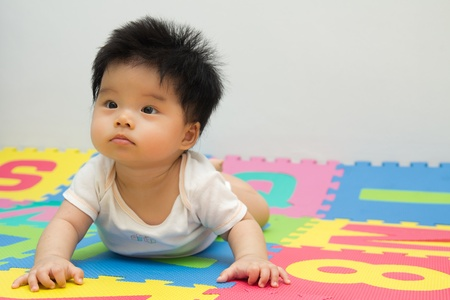 Portrait of a little Asian baby girl crawling on floor photo