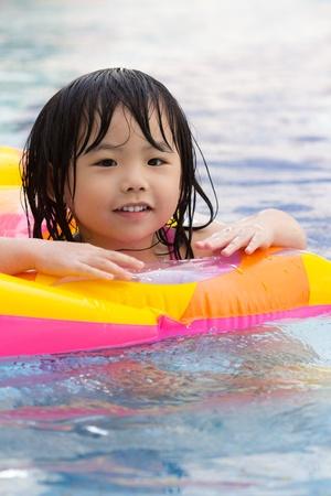 小さな女の子がプールで楽しんでください。
