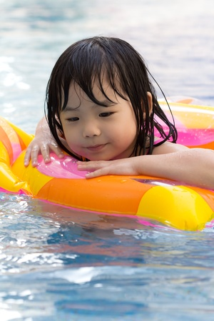 floater: Little girl is having fun in swimming pool Stock Photo