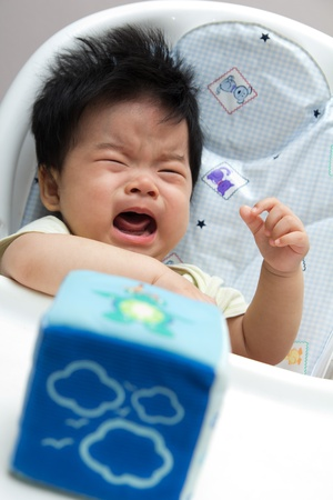 unsatisfied: Little Asian baby girl crying on a high chair