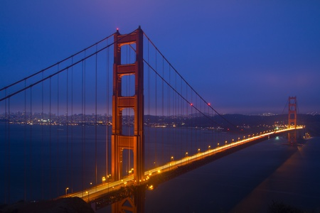 Golden Gate Bridge sunset evening with lights of San Francisco California in background photo