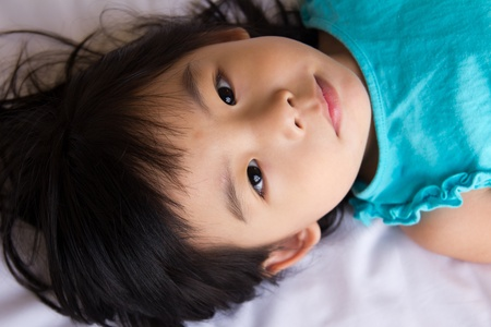 childishness: Portrait of the little girl laying on bed