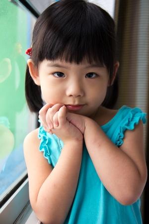 어린 소녀의 초상화 창 근처에 서있다