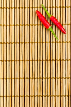 chili's restaurant: Two red chilli at the right corner of a bamboo mat, empty left space for text