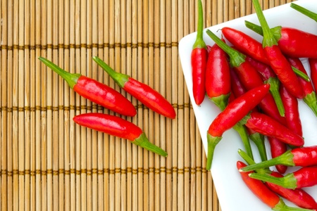 red chilly: Red chillies in a white plate on a bamboo mat Stock Photo
