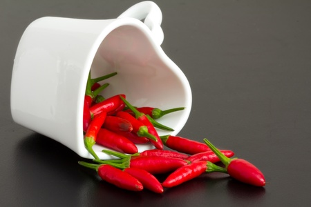 Red chillies in a heart shape cup photo