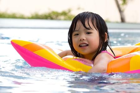 Little girl is having fun in swimming pool Stock Photo