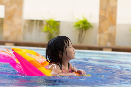 float tube: Little girl is having fun in swimming pool Stock Photo