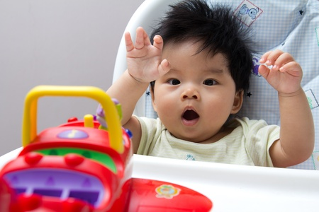asian baby girl: Little Asian baby girl on high chair playing with airplane toy