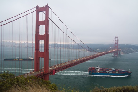 Container cargo ship passing underneath Golden Gate bridge photo