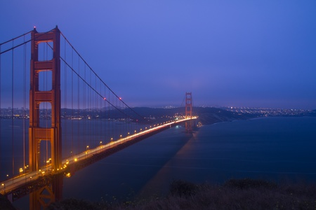 Golden Gate Bridge sunset evening with lights of San Francisco California in background