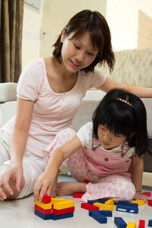 Happy mother and daughter playing with colorful blocks inside a house 版權商用圖片