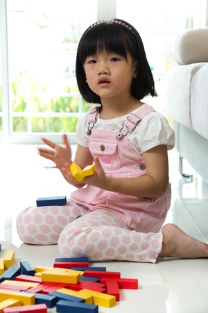 color block: Little Asian girl is playing with blocks toy