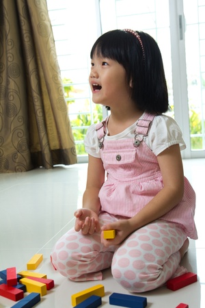 Little Asian girl is playing with blocks toy photo