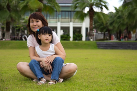 Lovely mother hugs her daughter, both sit on a green field Stock Photo