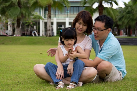 sits: Happy family of three sits on green grass field