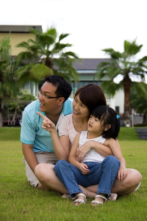 Happy family of three sits on green grass field photo