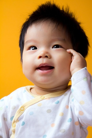 childishness: Portrait of a little Asian baby girl with yellow background Stock Photo