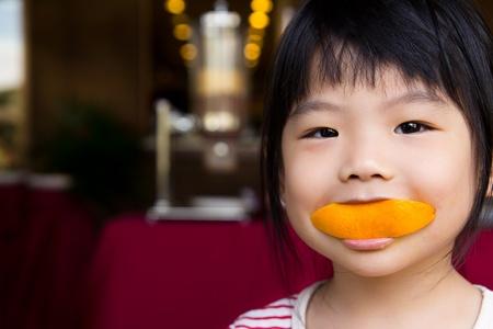 meisje eten: Schattig meisje het eten van een schijfje sinaasappel met een lachend gezicht Stockfoto