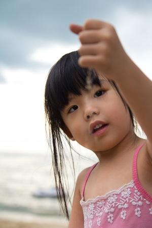 Little girl hold a handful sand in her hand and dropping it slowly photo