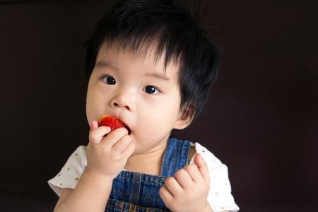 イチゴを食べる小さな女の赤ちゃんの写真