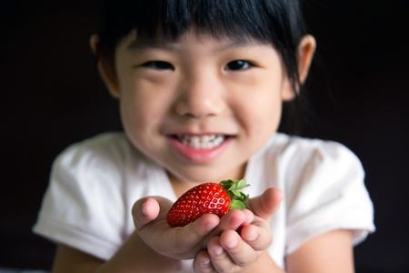행복 한 작은 소녀는 그녀의 손에 딸기를 넣어. 초점은 딸기에 있습니다.