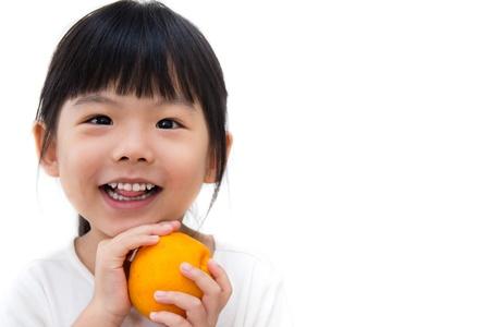 愛らしい少女の顔を笑顔でオレンジ色を保持しています。 写真素材