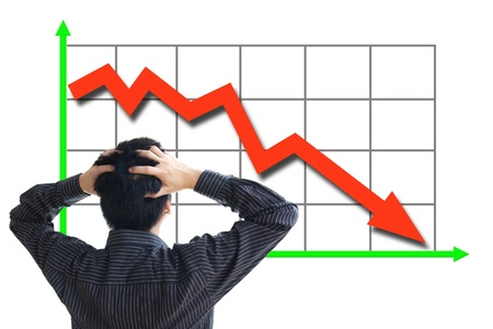 downturn: Frustrated business man looking at the falling graph of a stock market struck in financial crisis Stock Photo