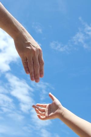 personas ayudando: Una mano de un adulto se extiende la mano para ayudar a los ni�os necesitados Foto de archivo