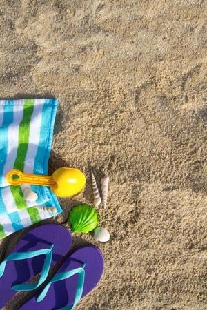Beach background with flip flop, towel and plastic spade photo