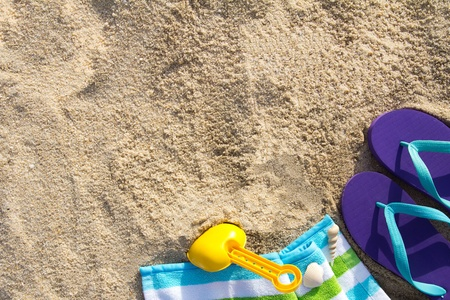 playtime: Beach background with flip flop, towel and plastic spade