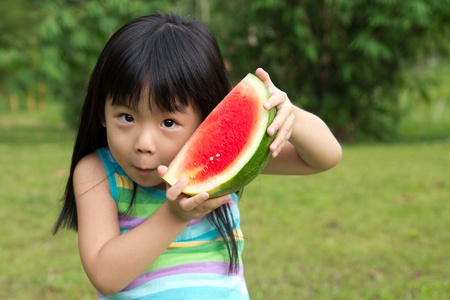 asia children: Little Asian kid with a piece of watermelon in park Stock Photo
