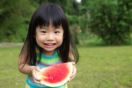 Little Asian kid with a piece of watermelon in park Stock Photo
