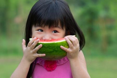 Little Asian kid with a piece of watermelon in park Standard-Bild