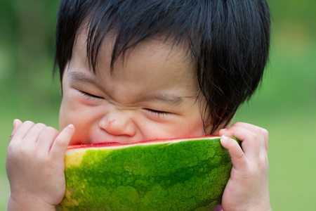 Little Asian baby eating watermelon in park