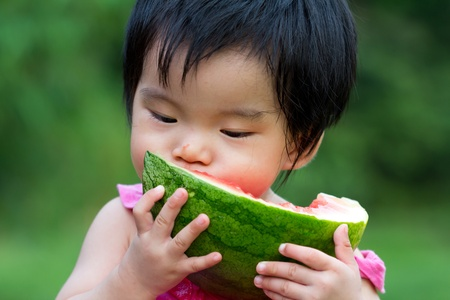 baby eating: Little Asian baby eating watermelon in park