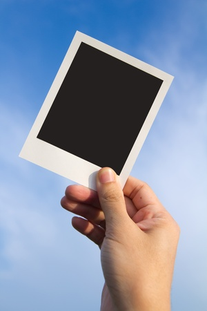 Hand holds a polaroid photo frame against blue sky photo