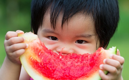Little Asian baby eating watermelon in park photo