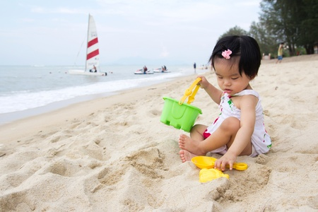 baby girl playing: Happy little baby girl playing sand on beach with bucket and spade