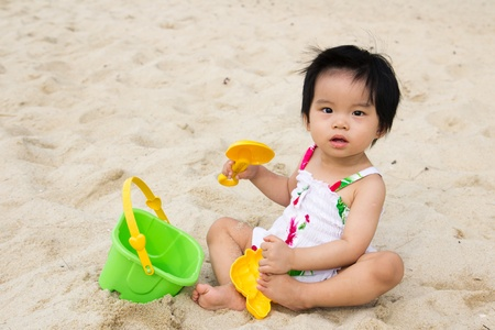 Happy little baby girl playing sand on beach with bucket and spade