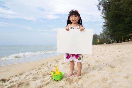 Weinig kind meisje houdt een wit bord op het strand