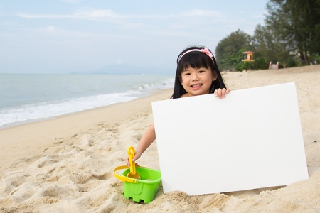 Little child girl holds a white board at beach photo
