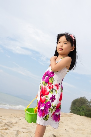Portrait of happy little girl holding a bucket and spade on beach photo