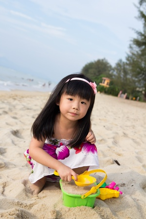 Happy little girl playing sand on beach with bucket and spade photo