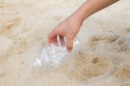 Hand picking up a plastic bottle from beach, cleaning up the beach