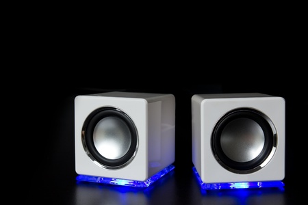 Electronic audio speakers isolated over a black background photo